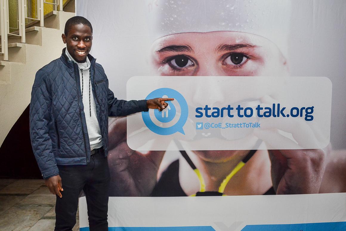 jovem em frente do imagem da campanha