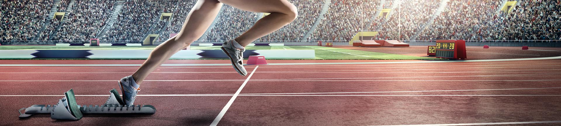 Atleta a partir de bloco de partida em pista de tartan
