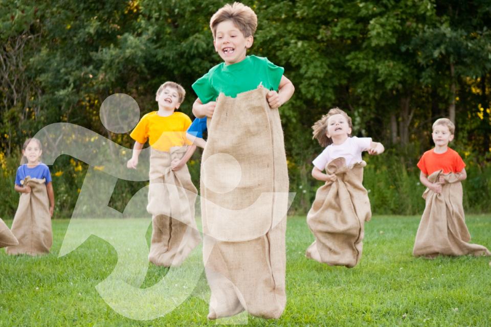 Jovens do 1.º ciclo a fazer uma corrida de saco num parque/jardim