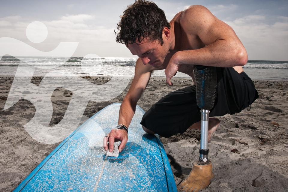 Jovem com deficiência motora a encerar a prancha de surf na areia