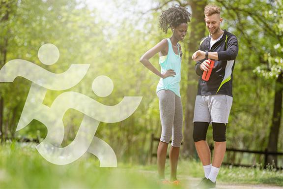 Dois jovens equipados com roupa desportiva olham para o cronómetro, num parque, ao ar livre.