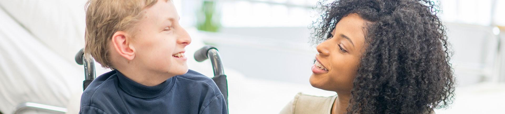 Plano de perfil de uma jovem e de uma criança em cadeira de rodas a conversarem