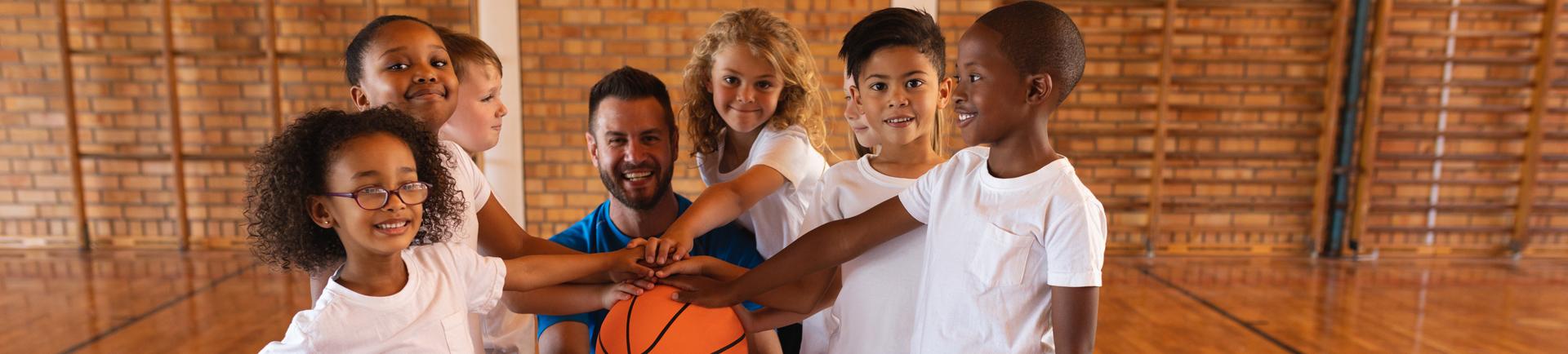 Jovens e treinador com as mãos à volta de uma bola de basquetebol