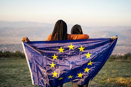 Jovens com a bandeira da União Europeia a fazer de capa