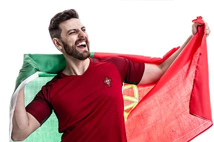 Jovem com camisola da seleção nacional com bandeira de Portugal às costas