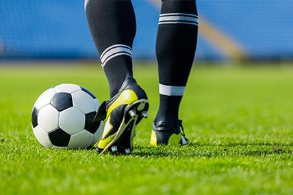 Imagem de pernas de jogador de futebol a preparar pontapé na bola