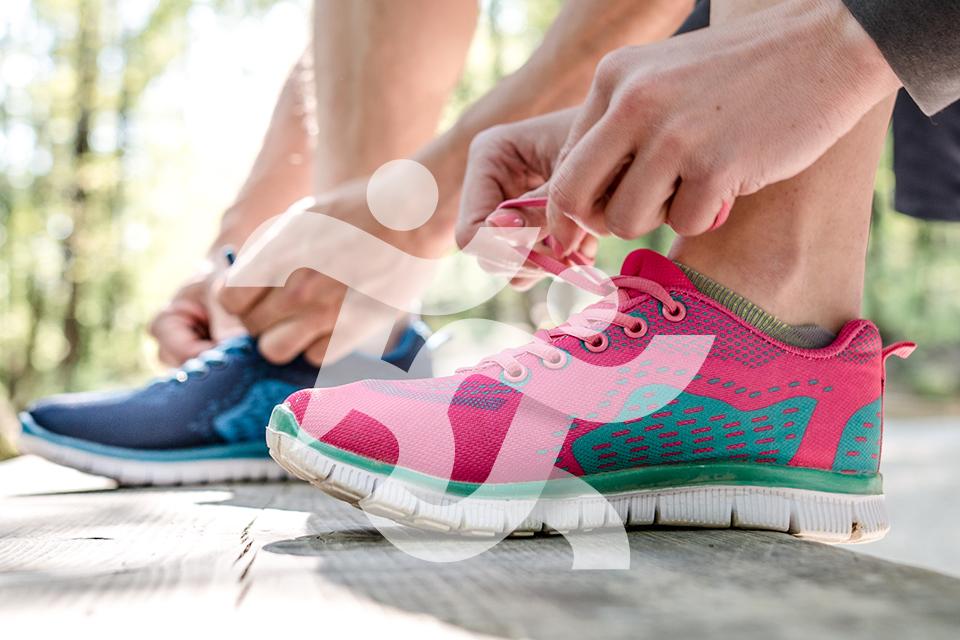 plano de pormenor de uma pessoa a atar os cordões de sapatilhas