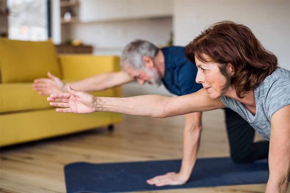 Casal sénior a praticar yoga na sala