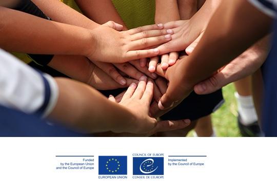 Circulo de mãos de jovens empilhadas e logos da União Europeia e Conselho da Europa