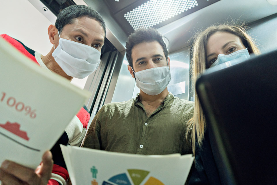 plano picado de três jovens de máscara a analisarem documentos