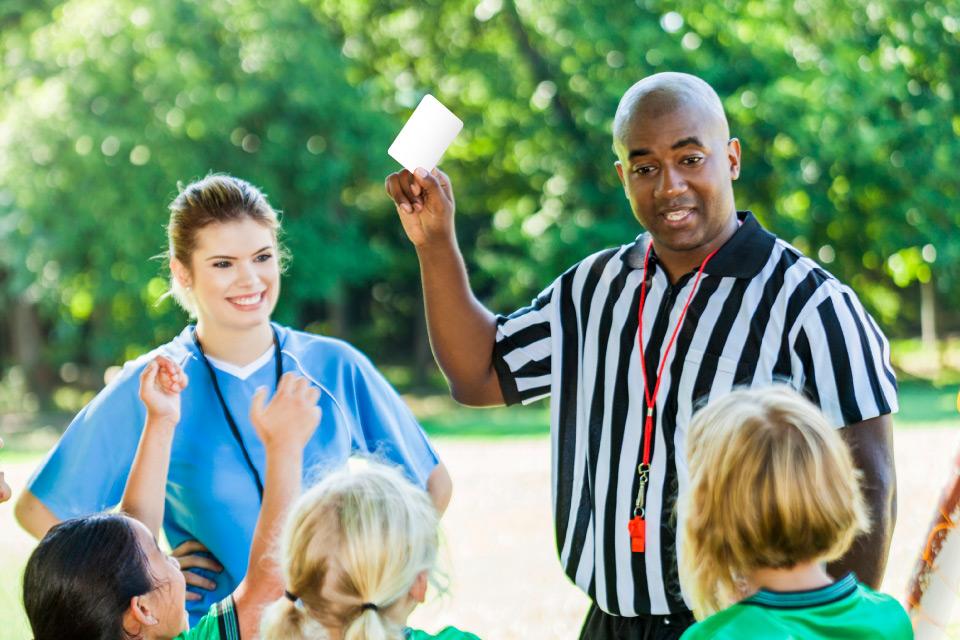 Árbitro, rodeado por um grupo de jovens, atribui o cartão branco a um jovem.
