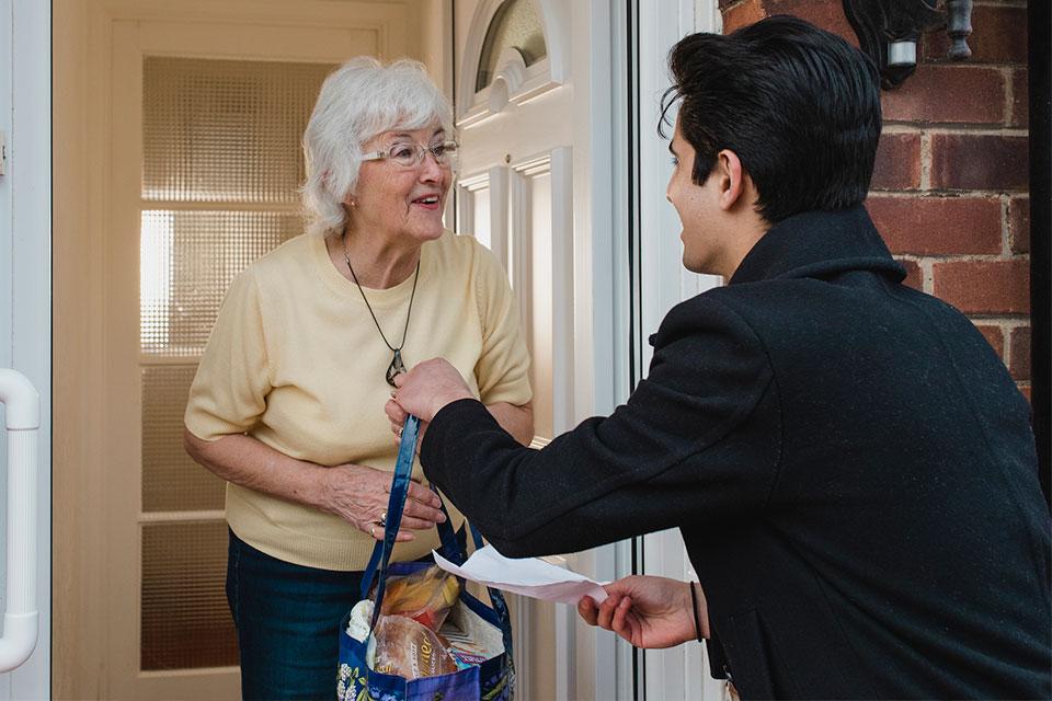 Jovem voluntário entrega saco de compras a uma idosa