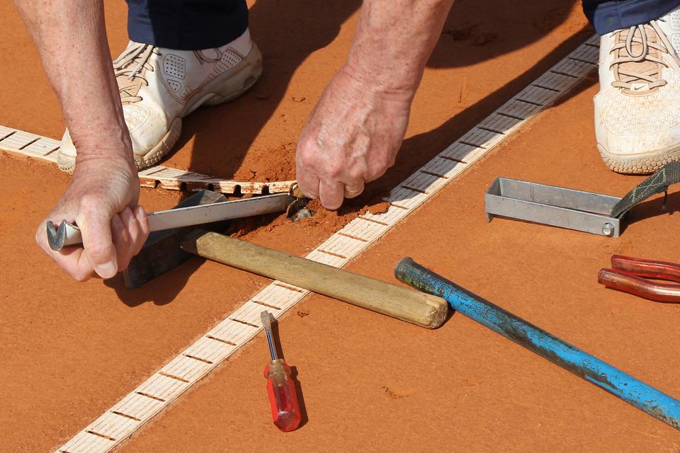 Plano de pormenor de umas mãos a construir num campo desportivo