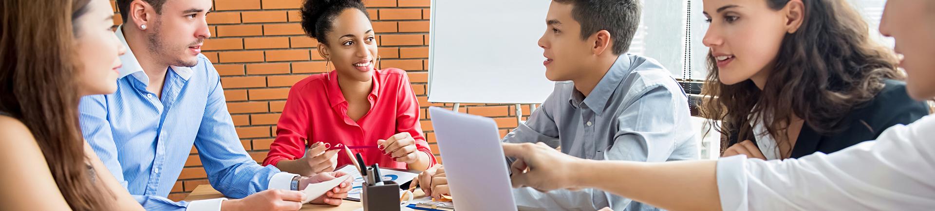 Jovens em reunião sentados à volta de uma secretária