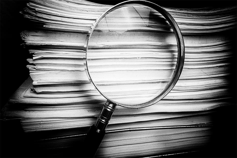 Pilha de documentos e lupa a investigar