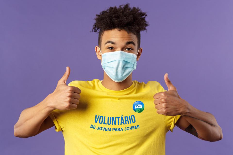"""Jovem com máscara e t-shirt amarela onde se lê """"voluntário de jovem para jovem"""""""