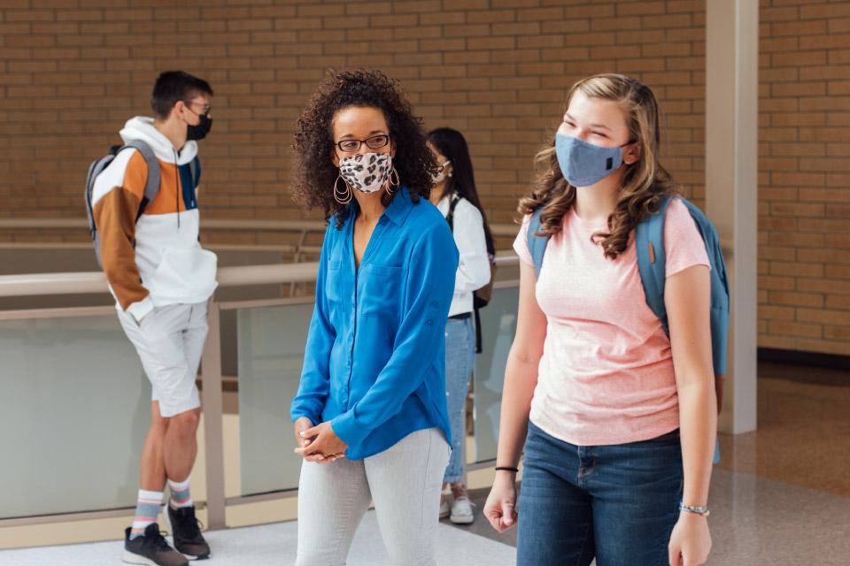 Duas jovens e um jovem com máscara, num átrio.