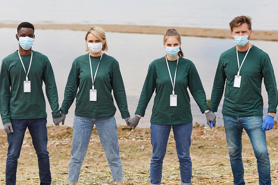 Dois jovens e duas jovens de mãos dadas afastados e com máscaras cirúrgicas azuis