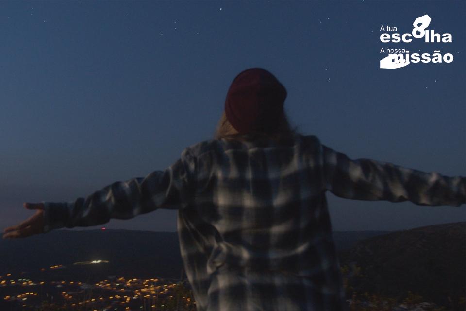 jovem mulher de braços abertos a olhar para um vale iluminado