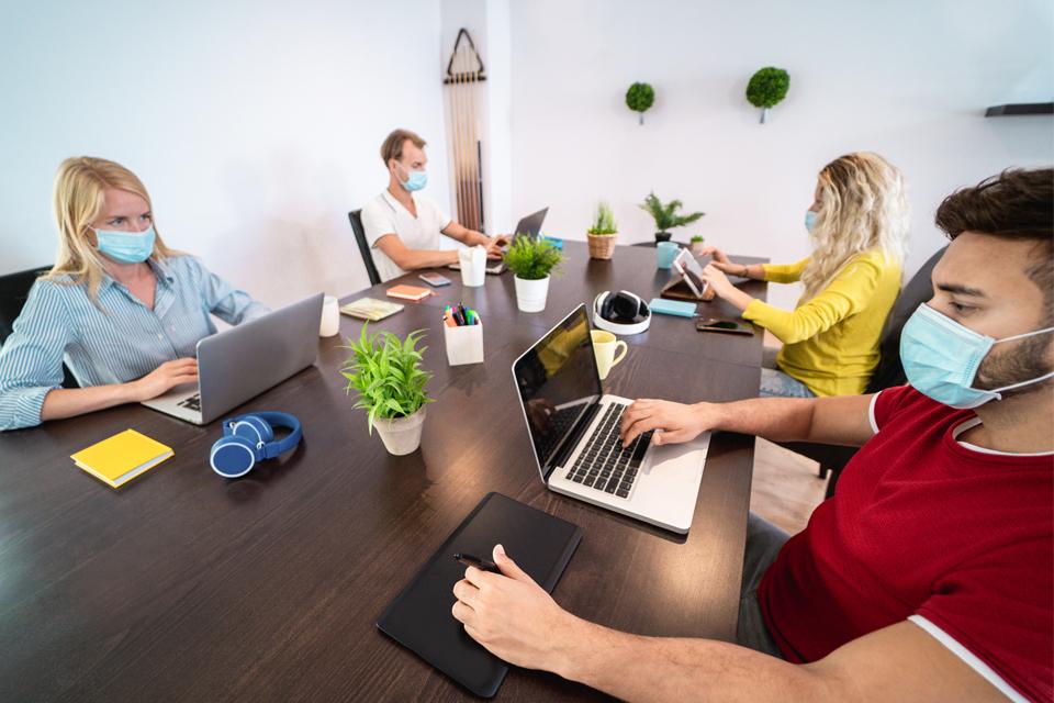 Quatro jovens a trabalhar à volta de uma mesa.