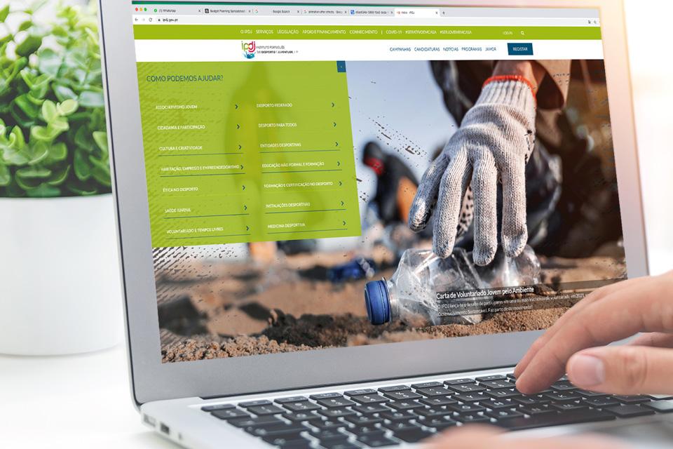 Mão sobre um teclado de um computador portátil com imagem da home page do portal IPDJ no ecrã.