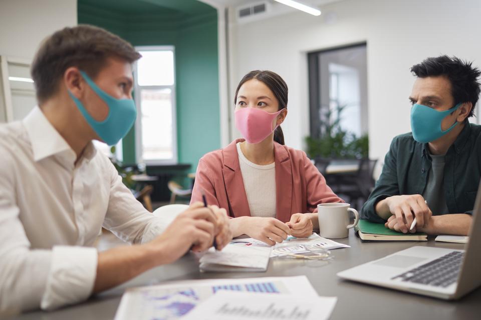 Três jovens, dois rapazes e uma rapariga com máscaras azuis e cor de rosa, respetivamente.