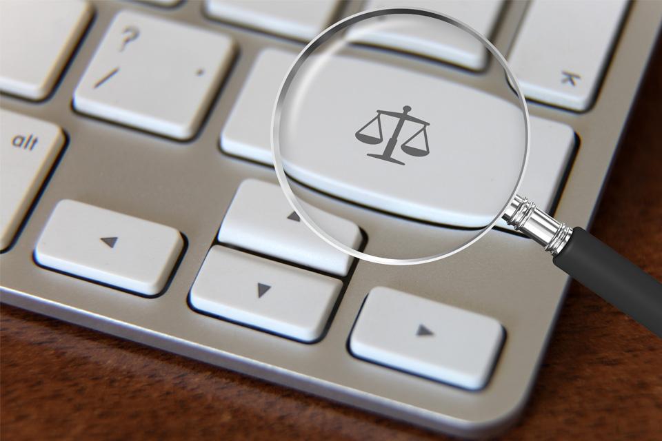 teclado de computador com uma lupa a incidir numa tecla com o símbolo da justiça (uma balança)
