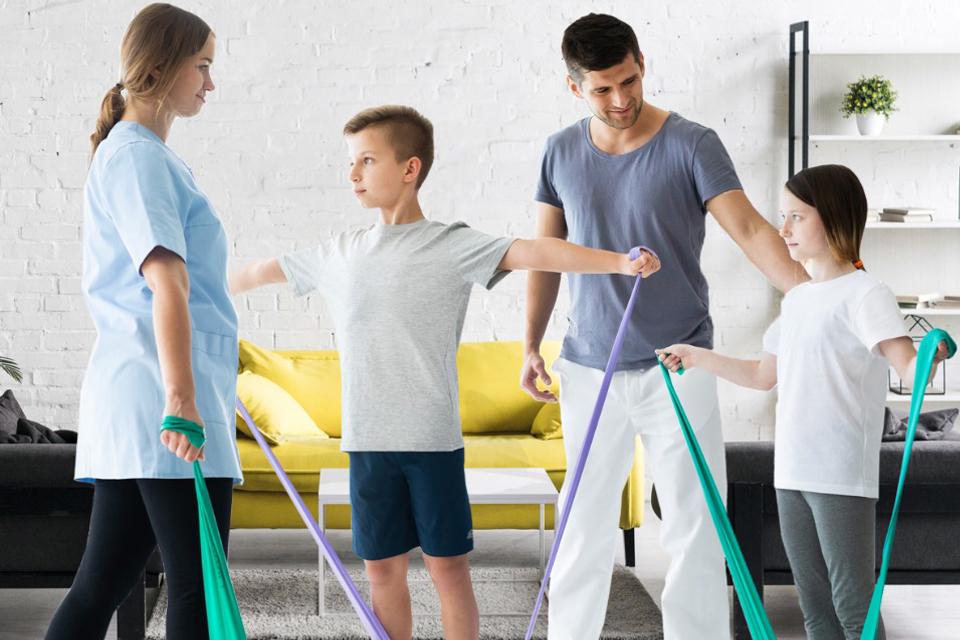 Familia (dois adultos e duas crianças) a praticar exercicio fisico em casa
