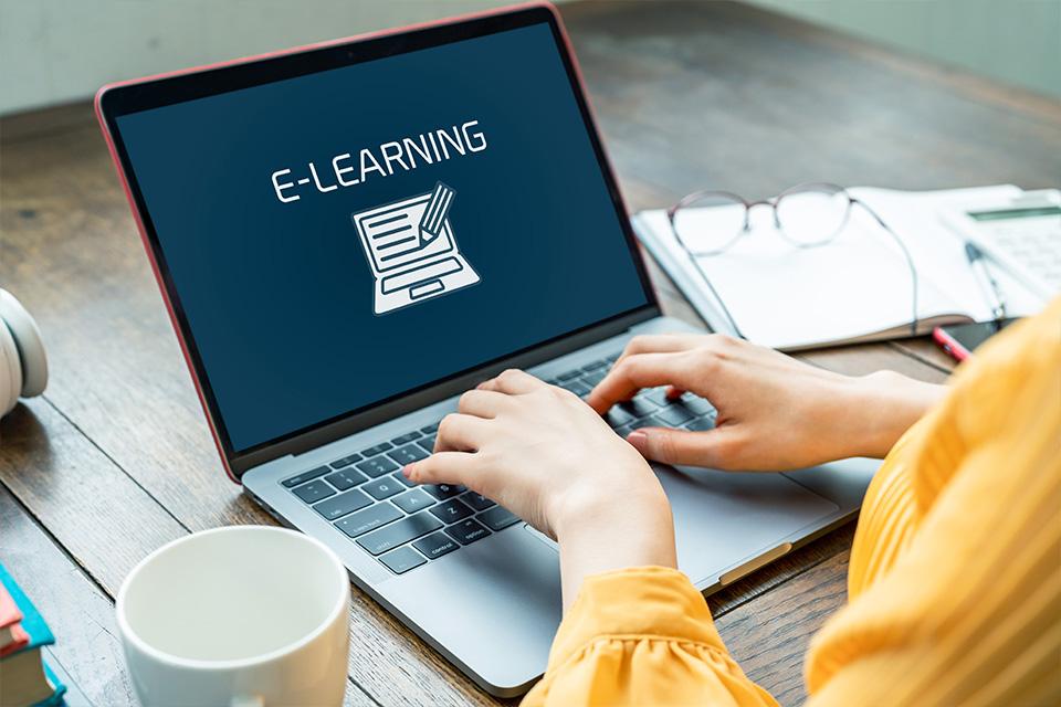 Mãos femininas sobre um teclado de um computador portátil. No ecrã está escrita a palavra «e-learning».