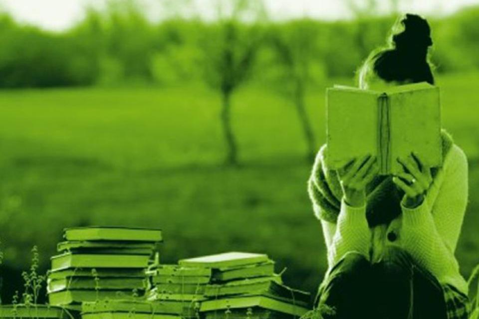 Jovem rapariga a ler um livro com um monte de livro ao lado.