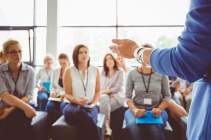 Imagem difusa de um conjunto de peessoas sentadas a ouvir outra que fala de pé e da qual só vemos as mãos.