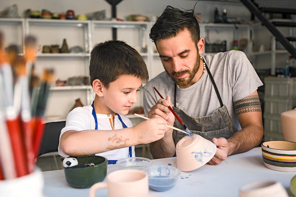Jovem a ensinar criança a pintar peça de barro