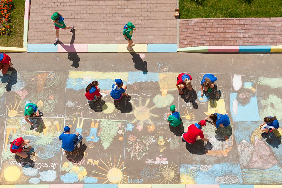 vista aérea de jovens a pintar com giz no chão de um espaço externo.