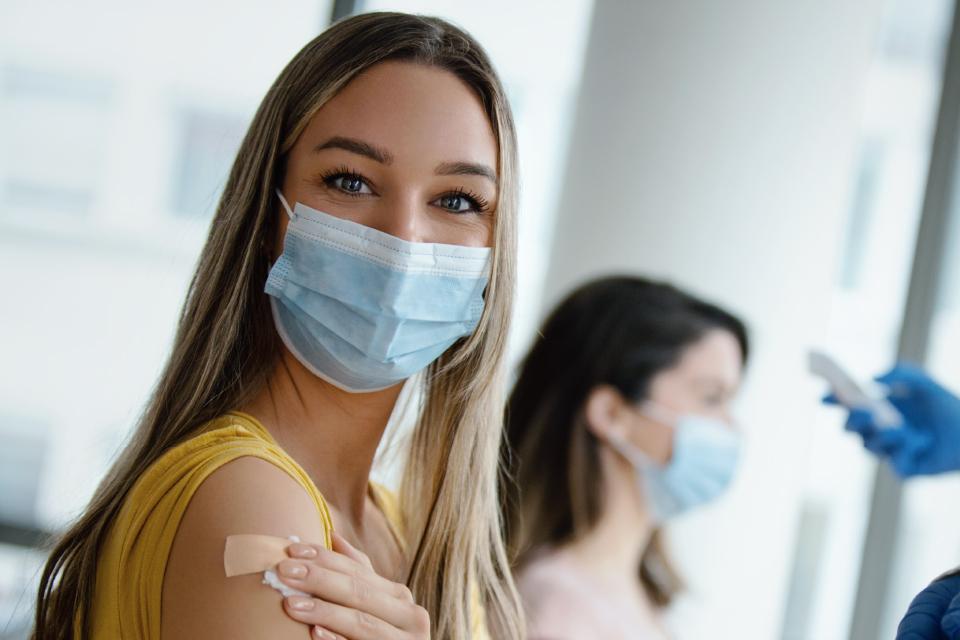 mulher jovem com mascara e a mãos no braço onde tem um penso
