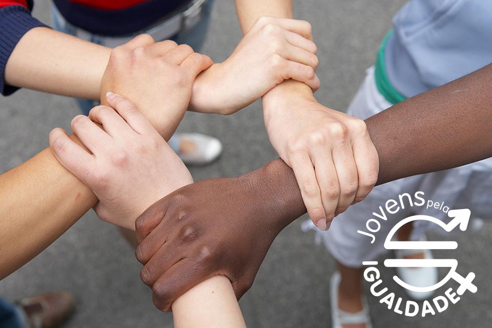 Mãos juntas, entrelaçadas pelos punhos e o logotipo concurso