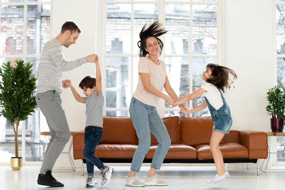 dois adultos e duas crianças brincam dentro de casa.